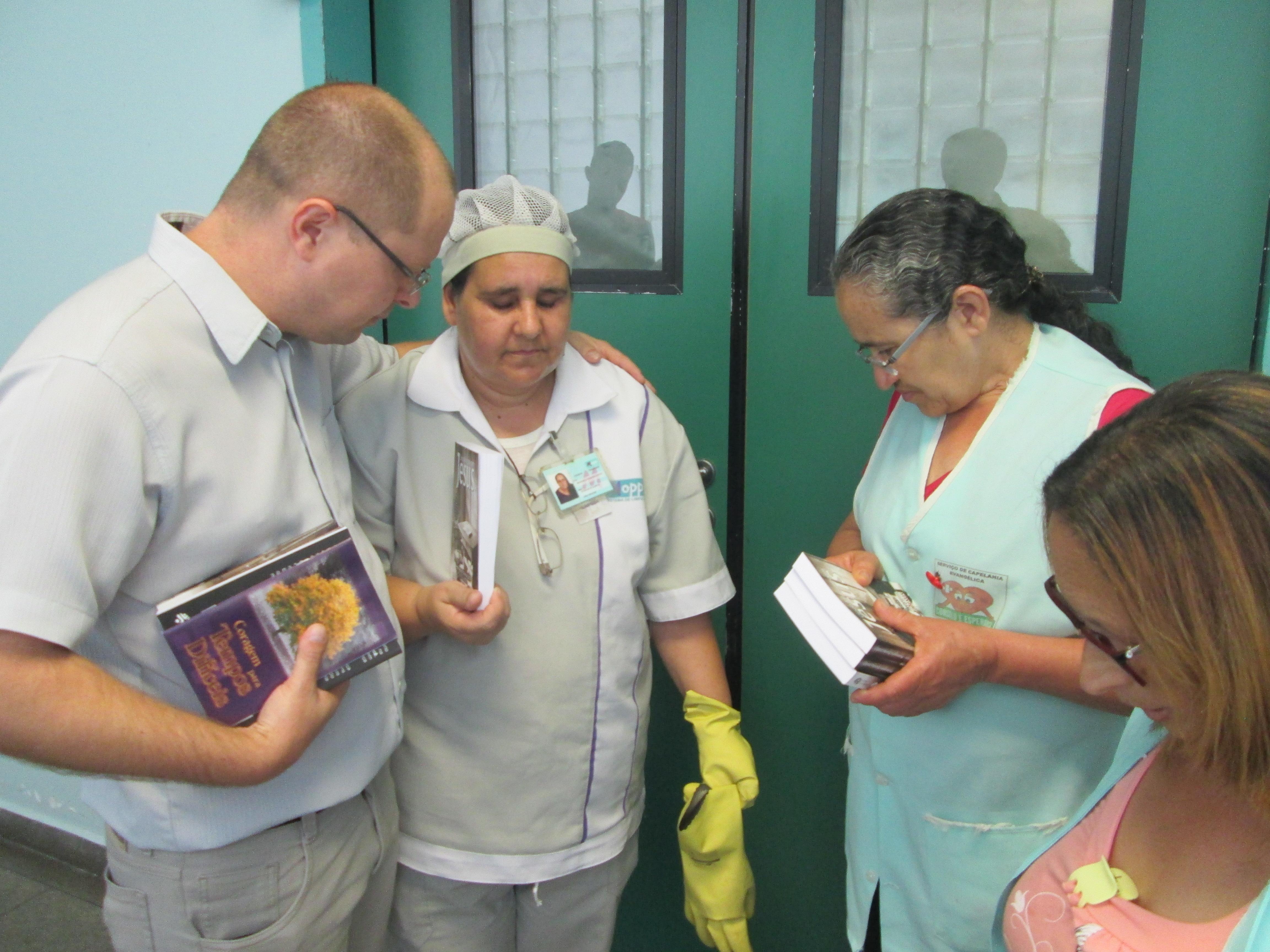 Pastor André orando com alguns funcionários.